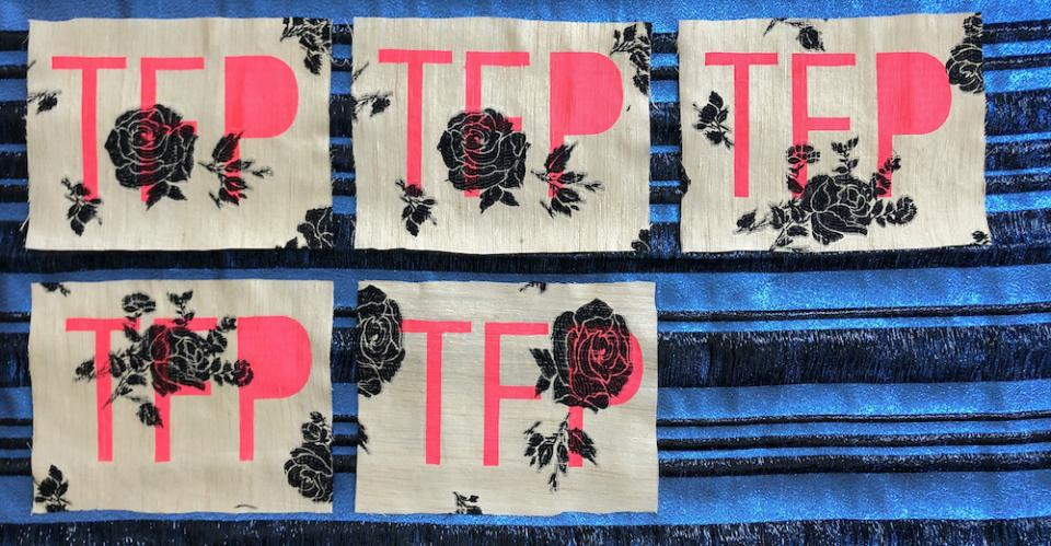 THE FUTURE IS PRESENT banner (Pink letters spelling TFP with block prints of black roses on canvas over a blue and black background)